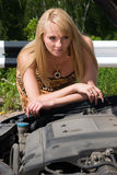 Young woman looks under a cowl. Young woman looks under a cowl of the car Stock Images