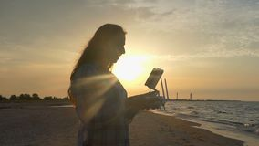 Young woman looks up with a flying drone panel at sunset in slo-mo. An impressive view of a young woman who looks up and keeps a control panel of a flying drone stock video footage