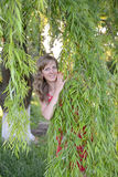 The young woman looks because of willow branches Stock Photography