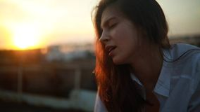 Woman with loose hair and closed eyes sings song at sunset. A young woman with loose hair and closed eyes sings song in white shirt at sunset stock footage