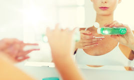 Young woman with lotion washing face at bathroom Stock Photo