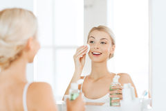 Young woman with lotion washing face at bathroom Royalty Free Stock Photo