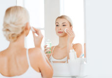 Young woman with lotion washing face at bathroom Royalty Free Stock Photos