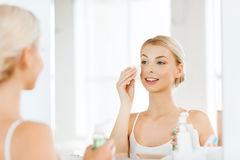 Young woman with lotion washing face at bathroom Royalty Free Stock Photography