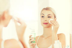Young woman with lotion washing face at bathroom Royalty Free Stock Images