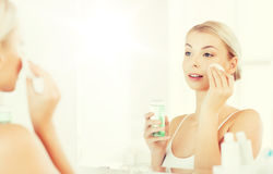 Young woman with lotion washing face at bathroom Stock Photography