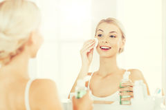 Young woman with lotion washing face at bathroom. Beauty, skin care and people concept - smiling young woman applying lotion to cotton disc for washing her face stock photos