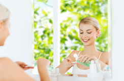 Young woman with lotion washing face at bathroom Royalty Free Stock Image