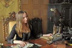 Young woman with lots of dollars in her hands and eagle on table Royalty Free Stock Photo