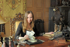 Young woman with lots of dollars in her hands and eagle on table Stock Photo
