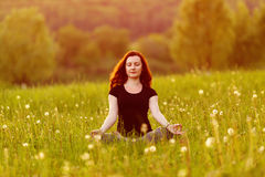 Young woman in the lotus pose on a evening meadow Stock Photography