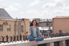 Young woman in a lotus position on the parapet Royalty Free Stock Images
