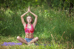 Young woman in lotus position in park Royalty Free Stock Image