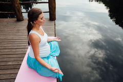 Young woman in the lotus position is practicing yoga in the forest next to the river. sitting on mats  the wooden pier. Stock Photos
