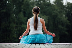 Young woman in the lotus position is practicing yoga in the forest next to the river. sitting on mats  the wooden pier. Royalty Free Stock Photos