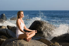 Young woman in lotus position on the stone Stock Photo