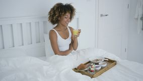 Content woman enjoying breakfast in bed stock video footage