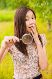 Young woman with a loupe Royalty Free Stock Photography