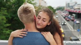 Young woman in love with closed eyes gently hugs her boyfriend in city. Slow motion stock video footage