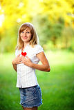 Young woman in love standing on nature holding a red paper heart Stock Photos