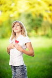 Young woman in love standing on nature holding a red paper heart Stock Photo