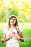 Young woman in love standing on nature holding a red paper heart Royalty Free Stock Photography