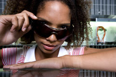 Young woman lowering sunglasses on nose, portrait, close-up Stock Image