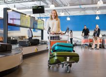 Young Woman With Luggage In Cart At Airport. Portrait of young women with luggage in cart walking by conveyor belt at airport Stock Photography