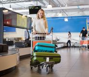 Young Woman With Luggage In Cart At Airport. Young women with luggage in cart walking by conveyor belt at airport Stock Image