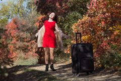 Young woman with the luggage on country road in the forest. Female person in short red dress and coat spinning arms outstretched. And looking up royalty free stock images