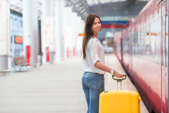 Young woman with luggage on train platform waiting Stock Photo
