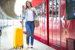 Young woman with luggage at a train station Stock Photos