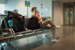 Young woman with luggage waiting in the airport hall her plane Royalty Free Stock Photography