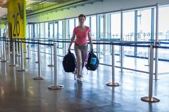 Young woman with luggage waiting in the airport hall her plane Stock Photo