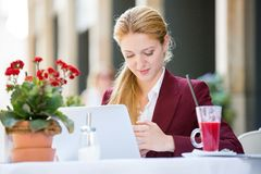 Young woman on lunch break. Young business woman talking on smartphone and working at the laptop. Drinking cocktail outdoors cafe in City with Happy smile Stock Photo