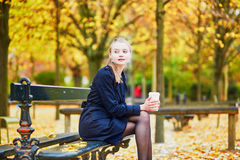 Young woman in the Luxembourg garden of Paris on a fall day. Beautiful young woman in the Luxembourg garden of Paris on a fall day, drinking coffee to go royalty free stock photo