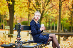 Young woman in the Luxembourg garden of Paris on a fall day. Beautiful young woman in the Luxembourg garden of Paris on a fall day, drinking coffee to go stock images