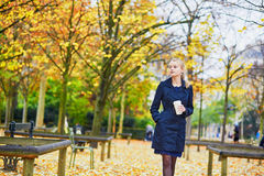 Young woman in the Luxembourg garden of Paris on a fall day. Beautiful young woman in the Luxembourg garden of Paris on a fall day, drinking coffee to go royalty free stock images