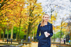 Young woman in the Luxembourg garden of Paris on a fall day. Beautiful young woman in the Luxembourg garden of Paris on a fall day, drinking coffee to go stock photography