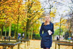 Young woman in the Luxembourg garden of Paris on a fall day. Beautiful young woman in the Luxembourg garden of Paris on a fall day, drinking coffee to go stock photo
