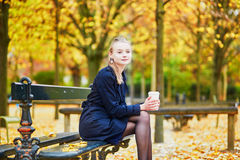 Young woman in the Luxembourg garden of Paris on a fall day. Beautiful young woman in the Luxembourg garden of Paris on a fall day, drinking coffee to go and stock photos