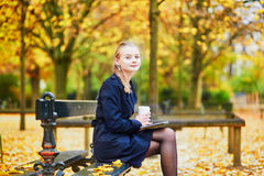 Young woman in the Luxembourg garden of Paris on a fall day. Beautiful young woman in the Luxembourg garden of Paris on a fall day, drinking coffee to go and royalty free stock image