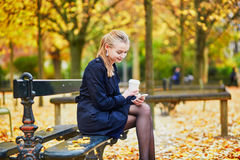 Young woman in the Luxembourg garden of Paris on a fall day. Beautiful young woman in the Luxembourg garden of Paris on a fall day, drinking coffee to go and stock photography