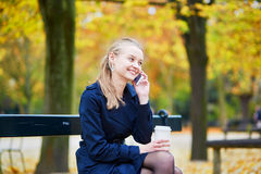 Young woman in the Luxembourg garden of Paris on a fall day. Beautiful young woman in the Luxembourg garden of Paris on a fall day, drinking coffee to go and royalty free stock photo