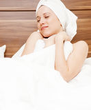 Young woman luxuriating in soft bed Stock Image