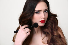 Young woman with luxurious dark hair and evening makeup. Fashion studio portrait of beautiful young woman with luxurious dark hair and evening makeup,holding stock photos