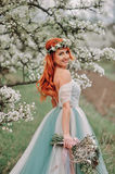 Young woman in a luxurious dress is standing and smiling in a blooming garden royalty free stock photo