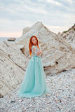 Young woman in a luxurious dress stands on the shore of the Adriatic Sea Stock Images