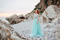 Young woman in a luxurious dress stands on the shore of the Adriatic Sea Royalty Free Stock Images