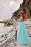 Young woman in a luxurious dress stands on the shore of the Adriatic Sea royalty free stock image
